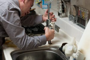 The Rooter Drain Expert Plumbers Repairing a line under the sink